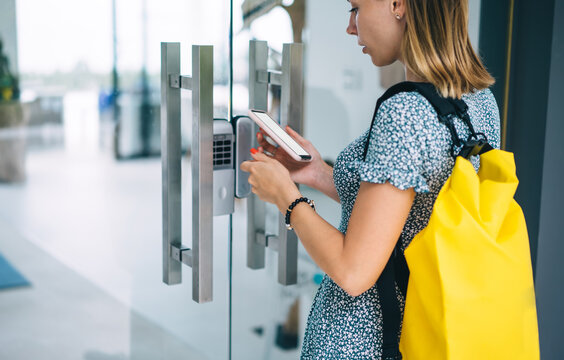 Young female unlocking door by smartphone