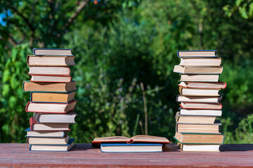 Stack of books on wooden table over nature background, outdoors