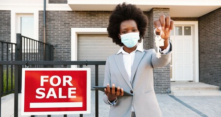Portrait of young African American beautiful woman real-estate agent standing outdoors at house...