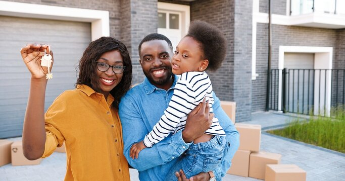 Portrait of happy African American family with small cute girl on hands standing at big house on suburb, smiling and showing key. Joyful mother, father with little pretty daughter. Moving in new home.