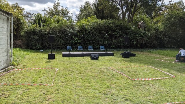 Outdoor concert set out with  1 meter squares marked on the ground to maintain social distance regulations during the COVID pandemic.
