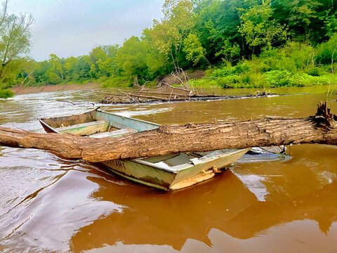 Abandoned boat on the river after a heavy rain