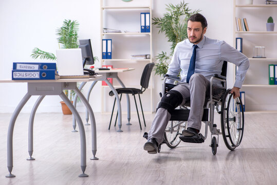 Young leg injured employee working in the office