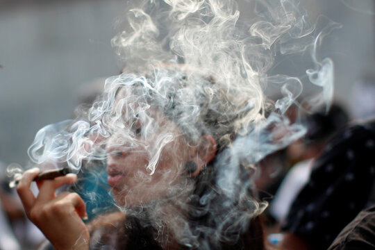 A pro-cannabis activist smokes marijuana as he takes part in a demonstration against the use of sniffer dogs inside the metro in Mexico City