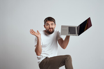 A man with a laptop in his hands on a light background in a white t-shirt emotions light background new technologies