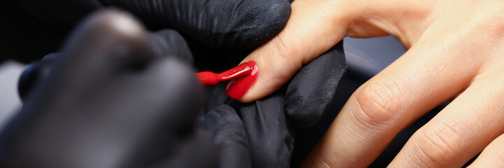 Female hand in black protective gloves make manicure closeup. Professional education concept