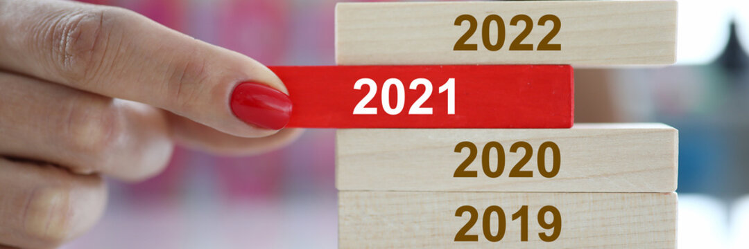 Female hand hold red wooden block with 2021 sign closeup. Chops and changes concept