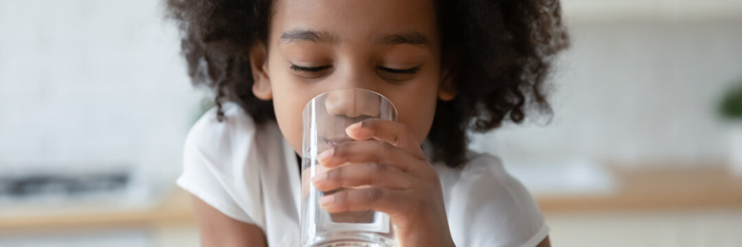 Thirsty funny small african ethnicity cute kid girl drinking fresh pure water, refreshing during day or enjoying morning healthcare routine, horizontal photo banner for website header design.