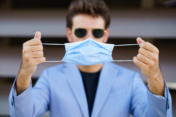 Businessman putting on a surgical mask to protect against the coronavirus.