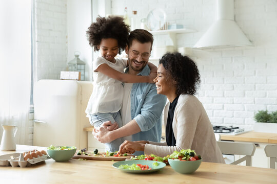 Smiling young european man holding on hands pretty small biracial adopted girl daughter, watching happy african american mother preparing healthy food, chopping fresh vegetables for salad in kitchen.