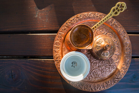 Pouring turkish coffee into vintage cup on wooden background. Traditional Arabic coffee.
