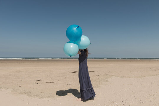 Young woman in blue dress with balloons standing on beach
