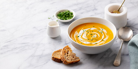 Pumpkin soup with cream. Marble background. Copy space.