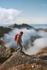 Man hiker trekking alone in mountains above clouds solo travel in Norway hiking adventure vacations trip outdoor healthy lifestyle concept