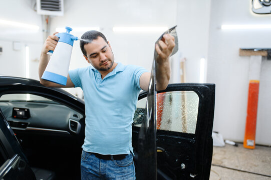 Male specialist with spray wetting car tinting