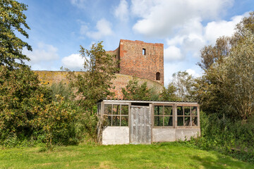 A small wooden shed in front of the ruin castle Teylingen in Sassenheim on a sunny and cloudy day in the Netherlands.