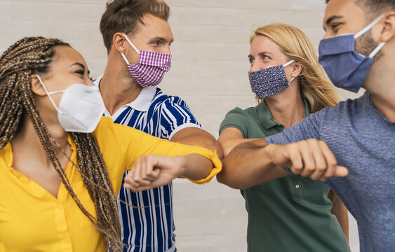 Young friends wearing face protective mask doing new social distancing greet with elbows bumps for preventing corona virus spread - Physical distance and friendship safety greetings concept
