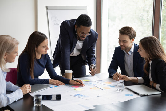 Multiethnic colleagues gather in boardroom brainstorm analyzing company financial paperwork together. Motivated diverse employees businesspeople talk discuss business project at team office meeting.