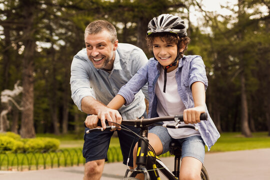 Boy learning how to ride bicycle with his happy dad