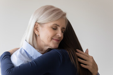 Happy Caucasian older 50s woman mother hug embrace grownup daughter reconcile make peace after fight. Smiling senior mom and adult girl embrace show love care in relationship. Family support concept.