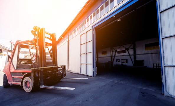 The big industrial forklift drives into the warehouse.