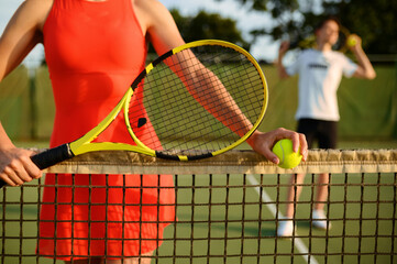 Male and female tennis players with rackets