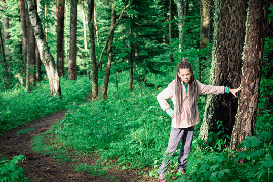 Cute girl on forest clearing among the trees on hike.