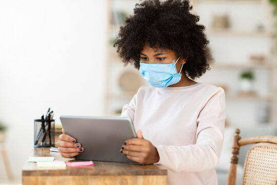 African Teen Girl Using Tablet Wearing Medical Mask At Home