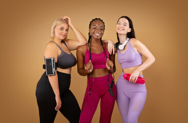 Smiling multiracial women with different figure type in sportswear over brown background