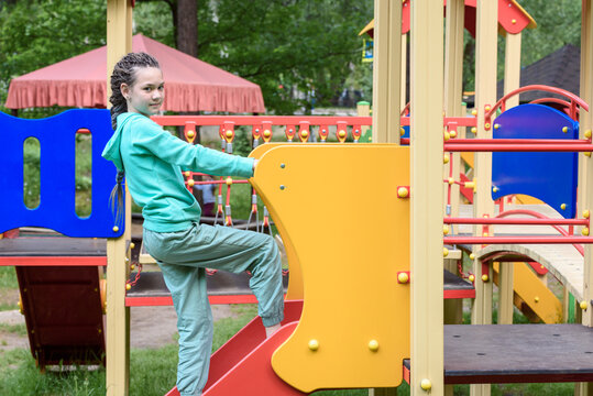 Girl with dreadlocks on hill at the playground.