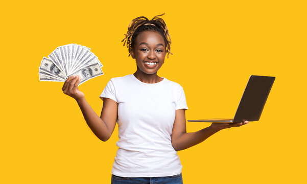 Joyful black girl with cash and laptop on yellow