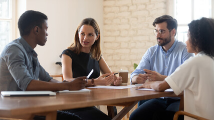 Young multiethnic colleagues sit at desk talk discuss ideas at work meeting in office, concentrated millennial diverse multiracial coworkers brainstorm cooperate at briefing, collaboration concept