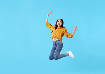 joyful young asian woman in yellow shirt jumping and celebrating over blue background.