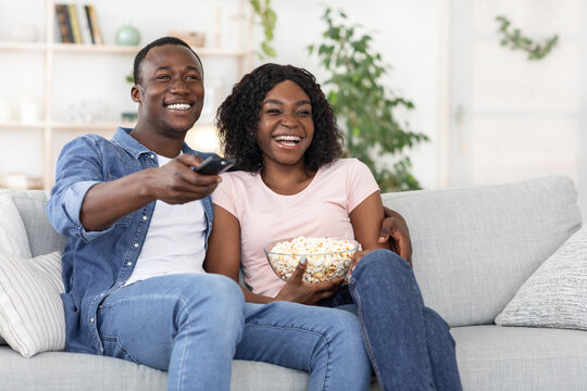Happy black family watching movie together at home