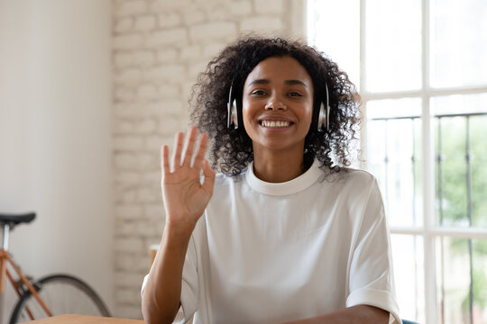 Headshot portrait of happy African American girl in headphones wave look at camera having video call, smiling biracial young woman in headset talk greet using laptop wireless Internet connection