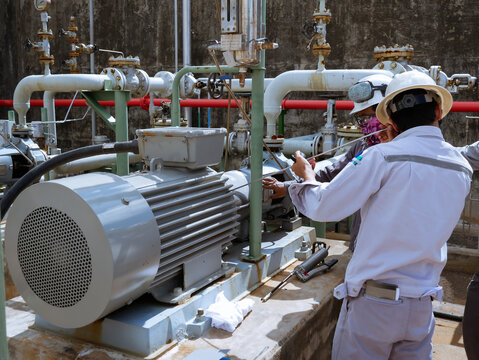 Technician checking and reading data vibration measurement of motor in power plant.