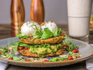 Two poached eggs on top of a vegetable stack at a table set for breakfast