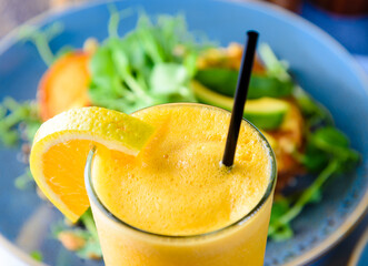 The top of a glass of orange juice, with a black straw and slice of orange, against a healthy green background
