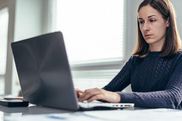 Woman in office at workplace working with laptop.