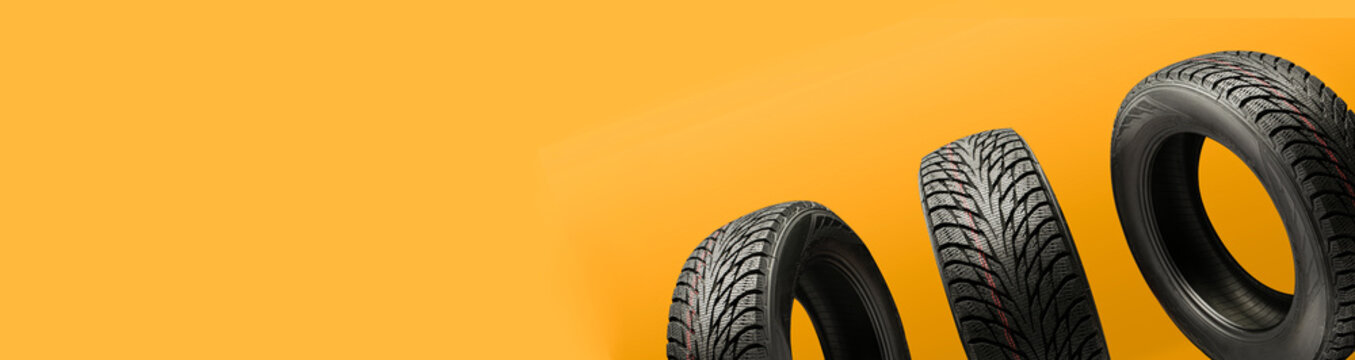 three friction tires, winter season re-booting, on a bright orange background. copy space panorama for the site header