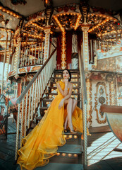 Young beautiful woman in a bright yellow evening dress sitting on stairs. Fashion model posing against the backdrop of an amusement park and carousel