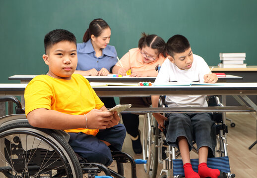 Asian disabled children Or, an autistic child learns to read, write and train their hand and finger muscles with a teacher at their classroom desk.