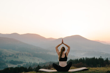 A young woman is practicing yoga at mountains. Relaxing in nature. Young girl doing yoga fitness exercise outdoor in the beautiful landscape. Morning sunrise, Namaste Lotus pose. Meditation.