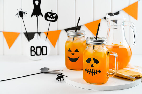 Halloween pumpkin iced mocktails in glass jars decorated with scary faces on a white table. DIY Halloween Party decoration on the wall. Party cocktails.