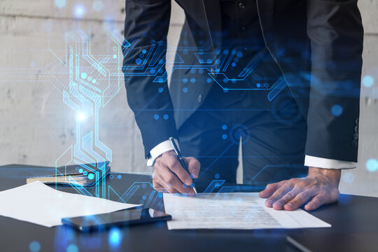 Businessman in suit signs contract. Double exposure with technology illustration hologram. New partnership in it business concept.