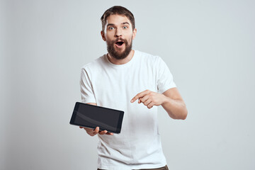 A man in a white T-shirt with a tablet in his hands emotions technology light background
