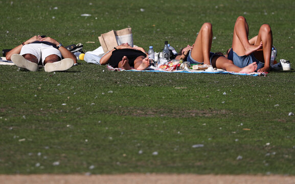 People take a rest on a sunny day on the grass in London