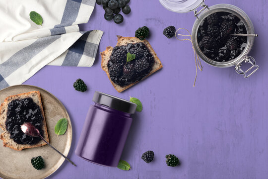 A breakfast scene with blueberry jam on bread. The purple tones with green highlights makes for a cheerful, vibrant background.