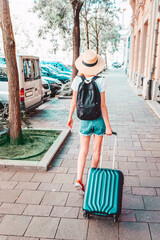 Rear view of young woman walking on the street with her suitcase while on city break
