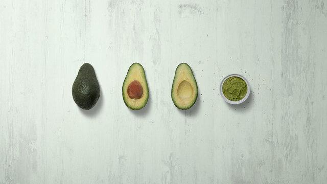 Avocado whole, avocado half, guacamole, on a green tinted wooden background